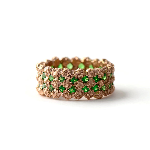 wide etternity ring made in rose gold and green garnets