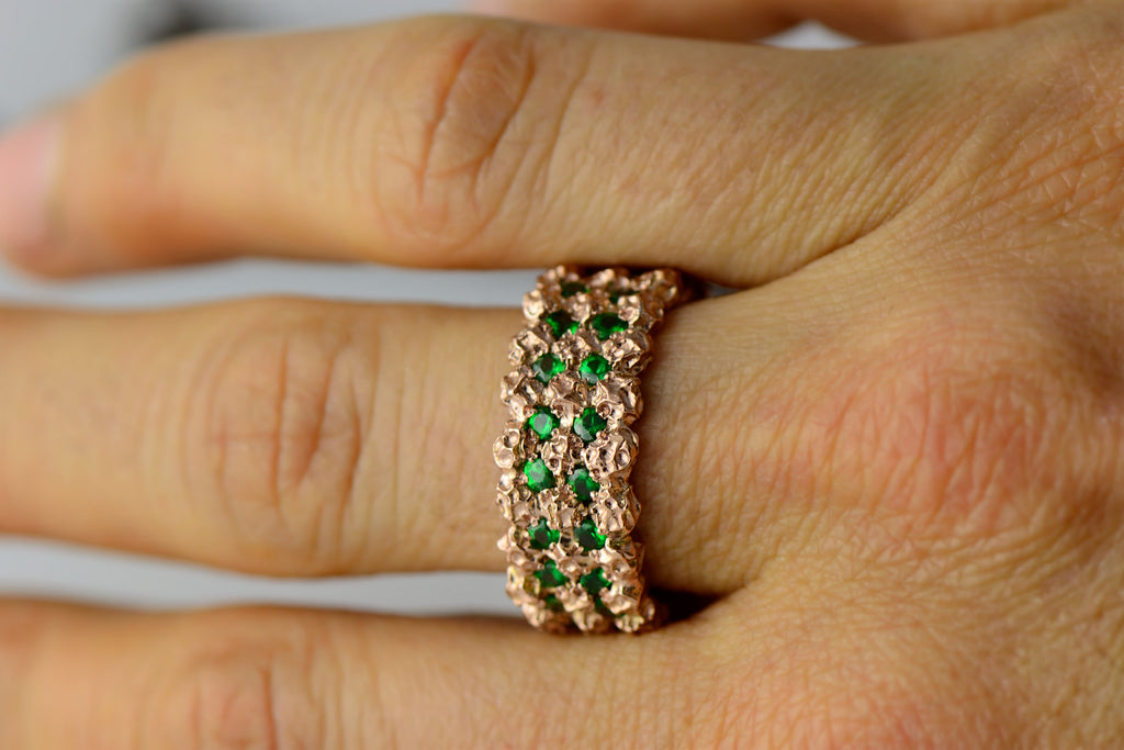 wide band in rose gold and green gemstones