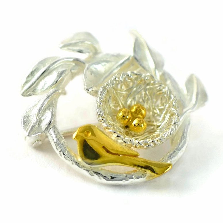 Bird's nest brooch with golden bird and nest eggs
