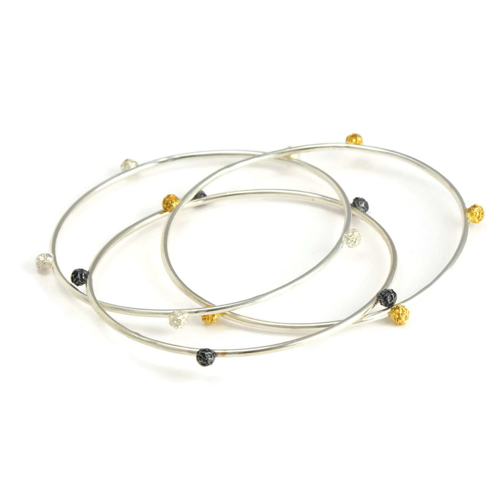A Set of three bangles, with stellar peppercorns design accented with gold vermiel, dark and bright silver sterling