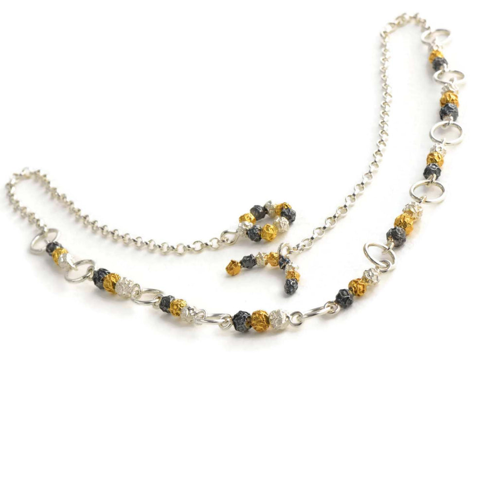 A silver and golden three peppercorn stick necklace