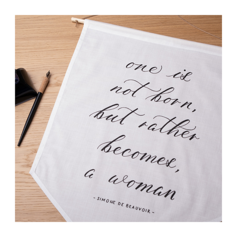 "Hand-calligraphed ""One is not born, but rather becomes a woman"" on linen banner with nib and ink on the side"