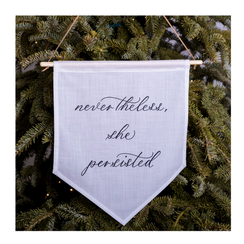 "Hand-calligraphed ""Nevertheless, she persisted"" on linen banner hung on a pine tree"