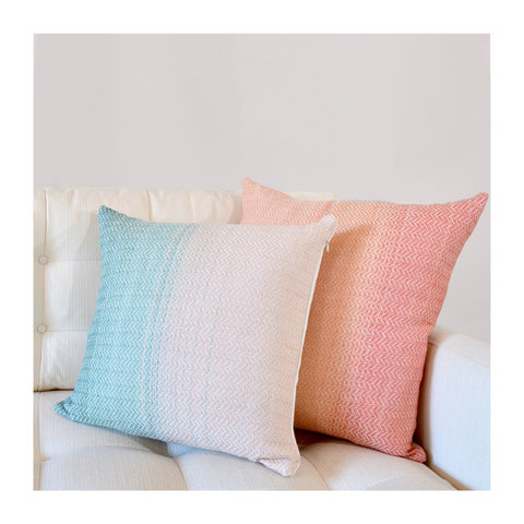 Two handwoven throw pillows, green and pink, on a white couch