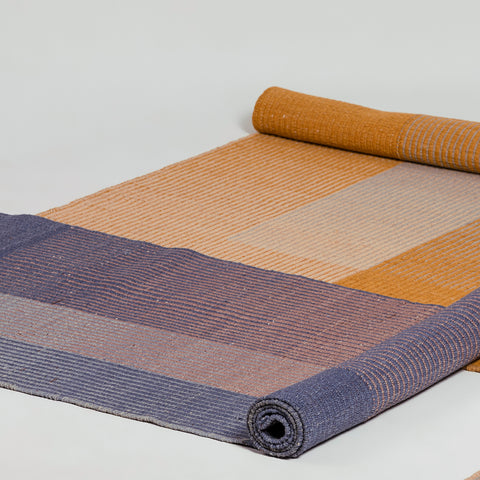 Two flatweave runner rugs half rolled on the floor