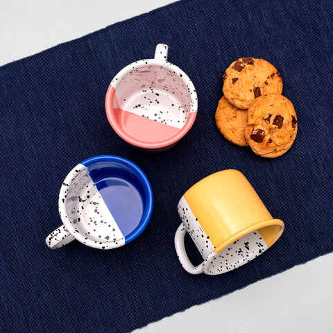 Three enamel mugs in blue, pink and yellow