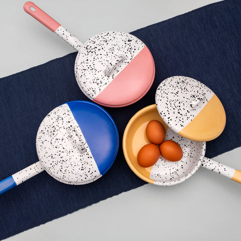 Three casserole pans in blue, pink and yellow