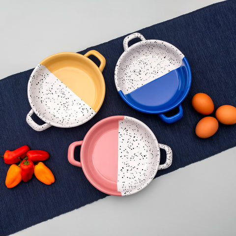 Three small frying pans in blue, pink and yellow