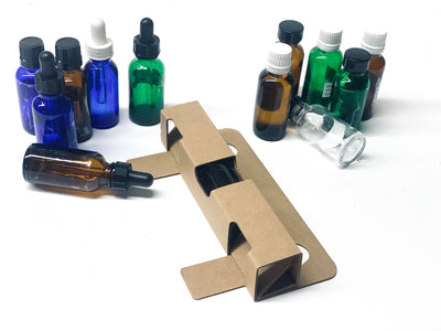 1 oz Bottle Shipper Insert folded and laying flar next to assorted 1 oz bottles