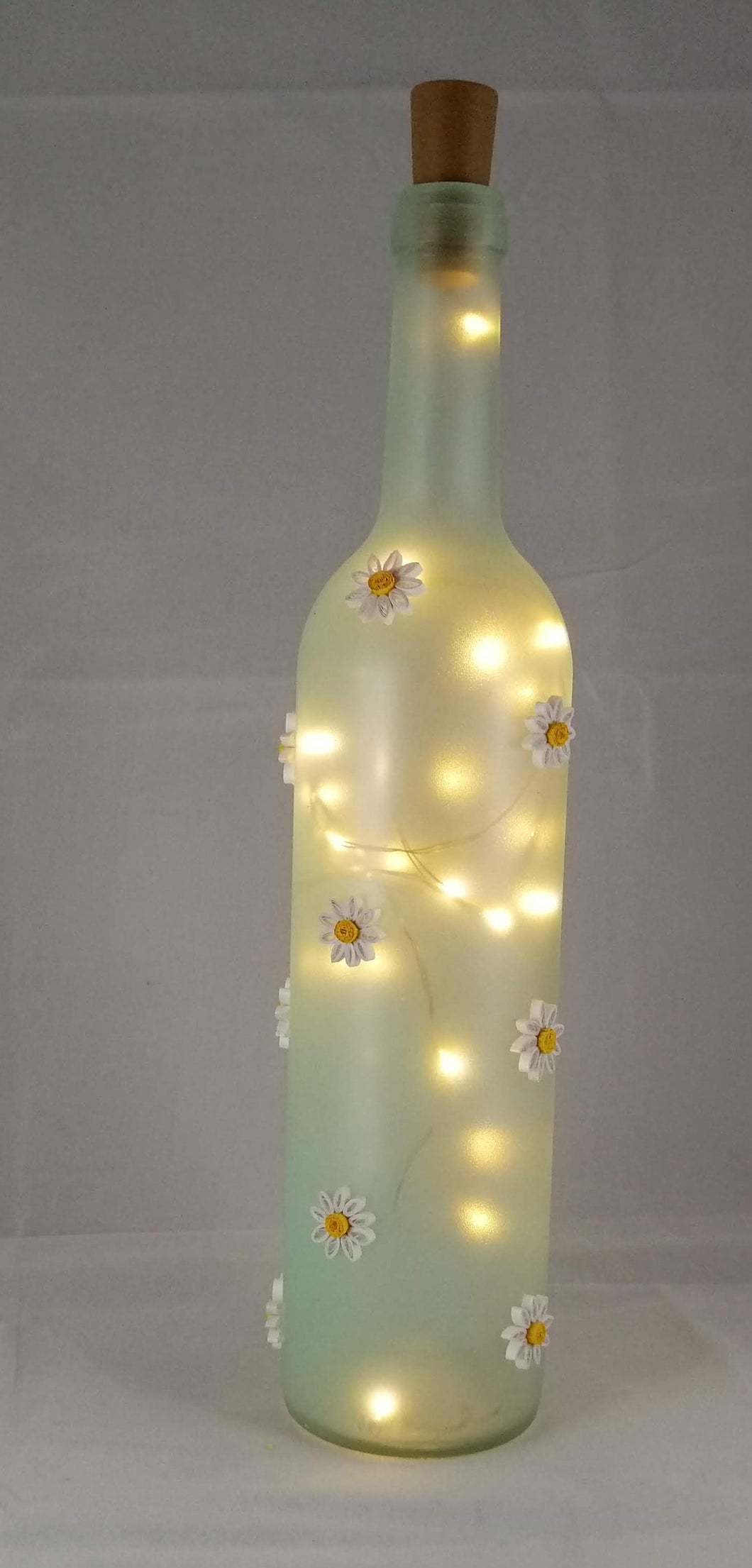 Glass bottle with daisies and lights