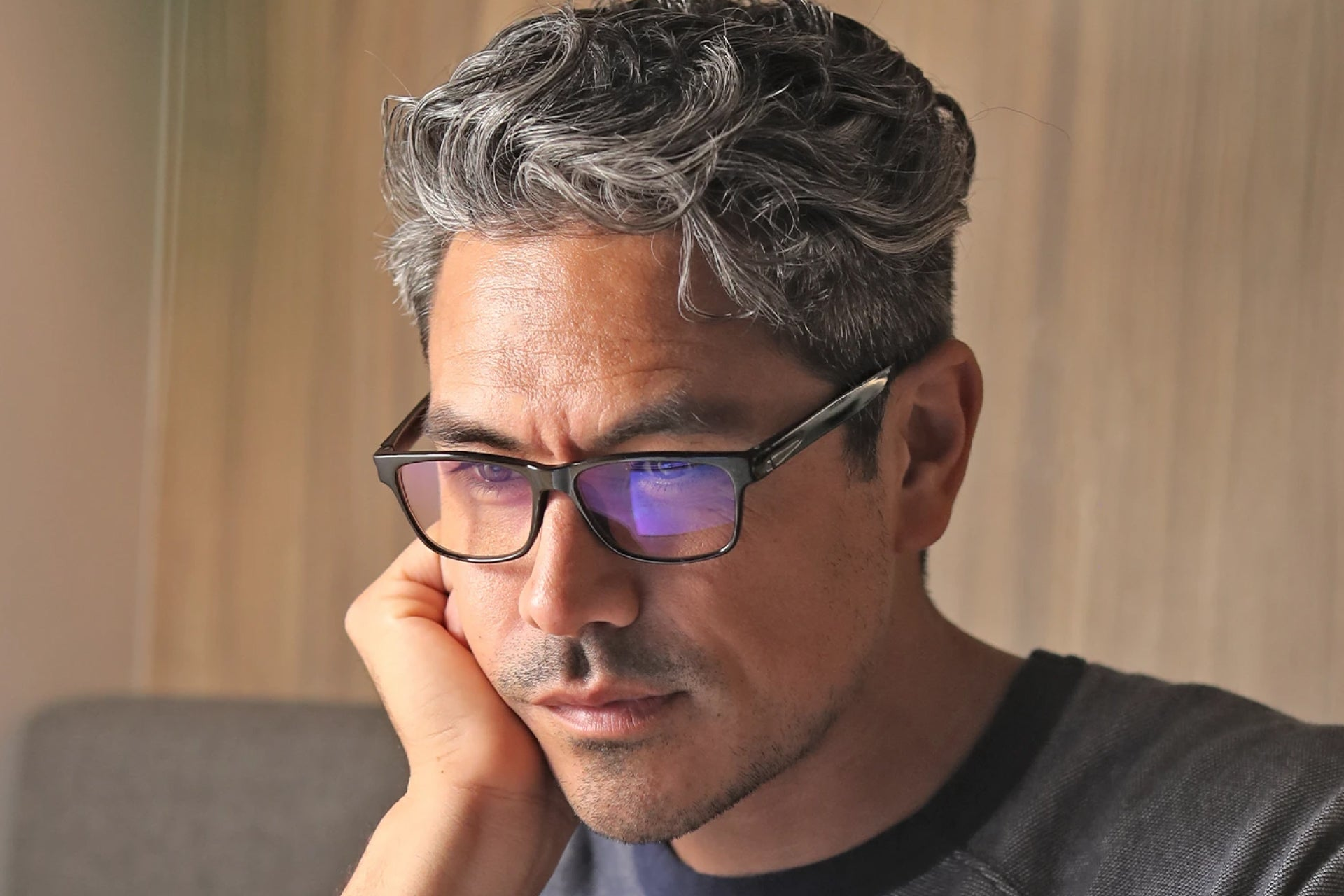 man looking at his computer wearing a pair of blue light glasses