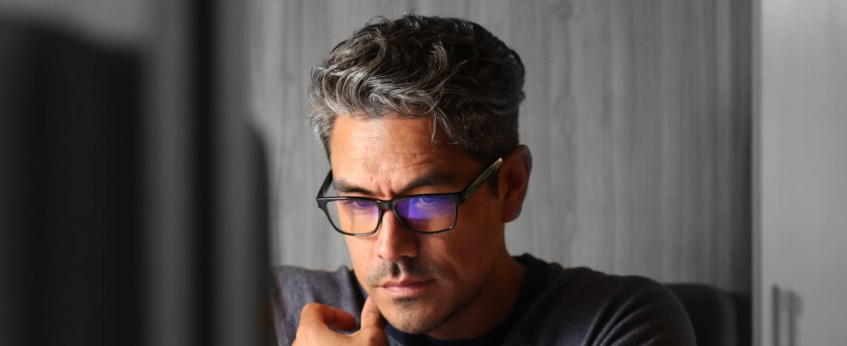 man wearing a pair of blue light glasses with a black frame