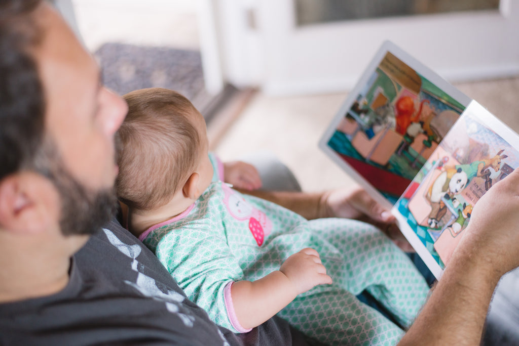 Father and Baby reading in the couch.