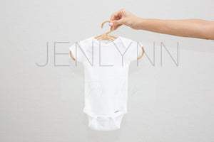 Woman Holding White Onesie on hanger Mockup #5 JPG