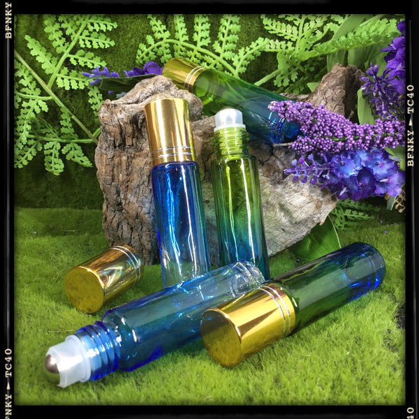 blue and green and blue and clear multiple glass vial roller ball perfume bottles displayed on green woodland background with purple flowers