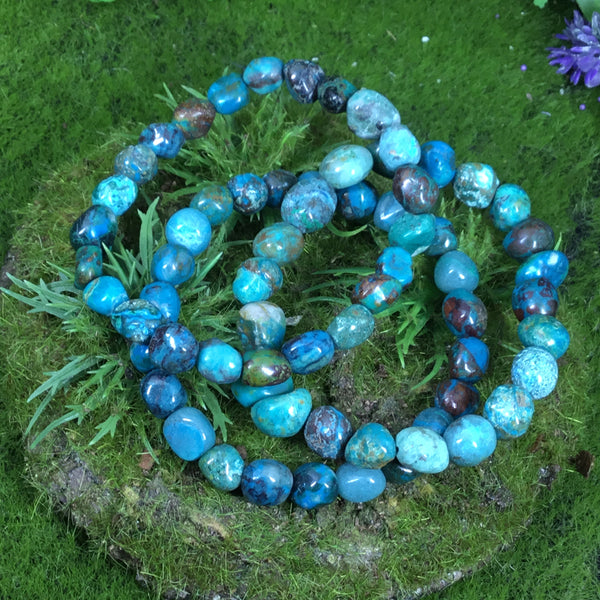 chrysocolla bracelets on green woodland background
