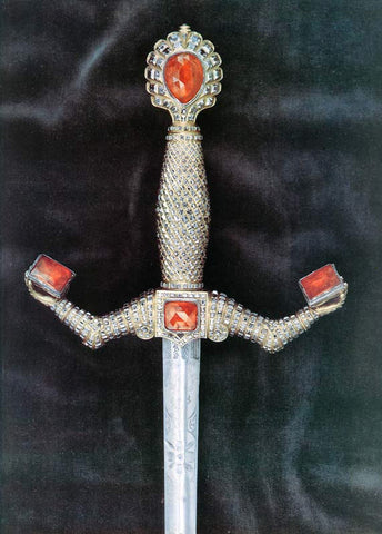 Jeweled sword hilt with anatomical arms.