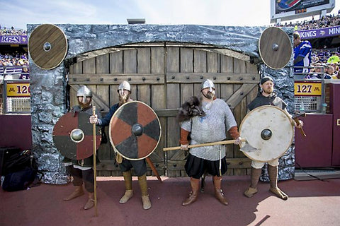 Viking reenactors at a Vikings Game with some A&A shields in the background.