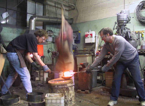 Three man forging a large shaped pommel with sledge and form.