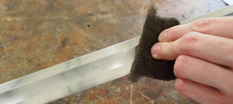 Grey scotchbrite pad used to clean blade.