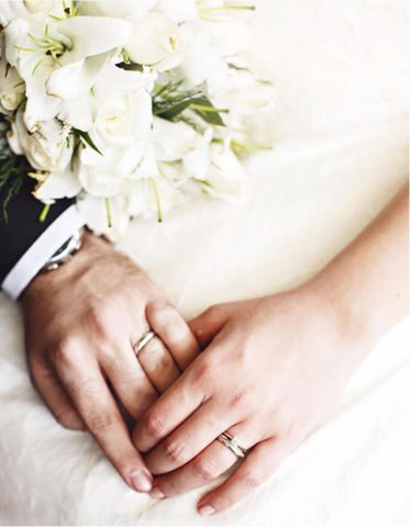 groom & bride holding hands with wedding bands showing