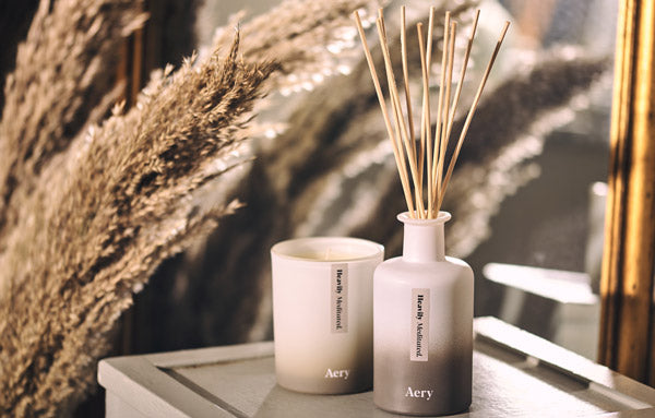 Aery Living Reed Diffuser and Scented Candle on a side table with decorative pampas grass
