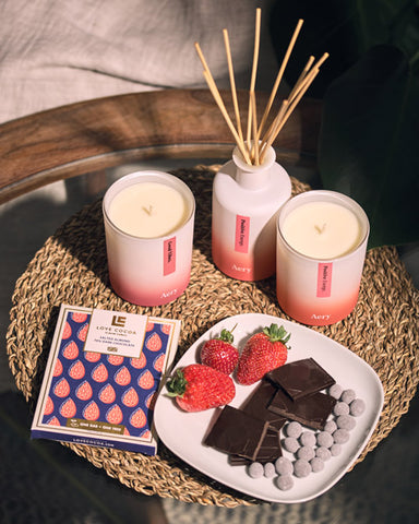 Aery red and white candles and diffusers on a coffee table next to a plate of love cocoa chocolates and strawberries