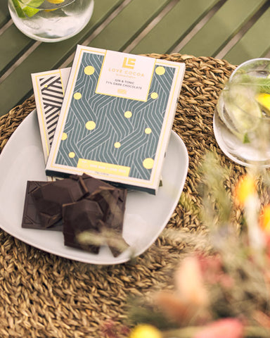 Bars of love cocoa chocolate on a table next to drinks and flowers