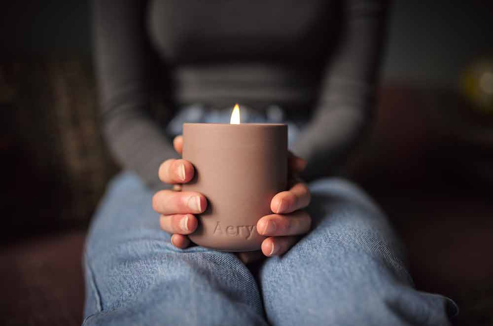 aery living moroccan rose scented candle in dusty pink clay being held in a persons lap