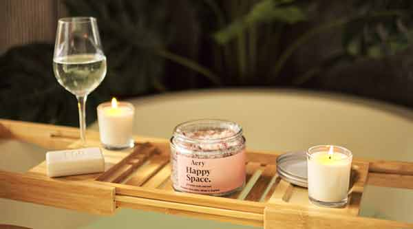 bath caddy with jar of bath salts, two miniature candles and glass of white wine
