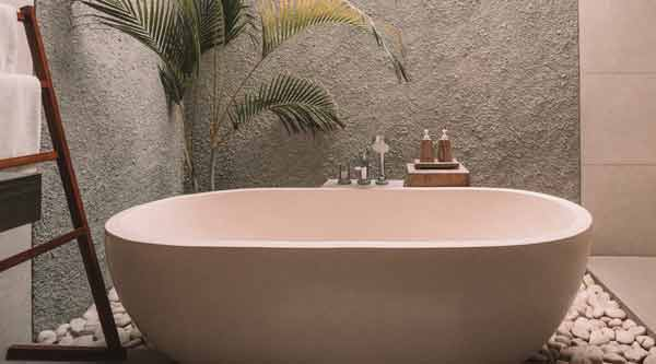 stand alone bath tub surrounded by palm plants in an open bathroom setting