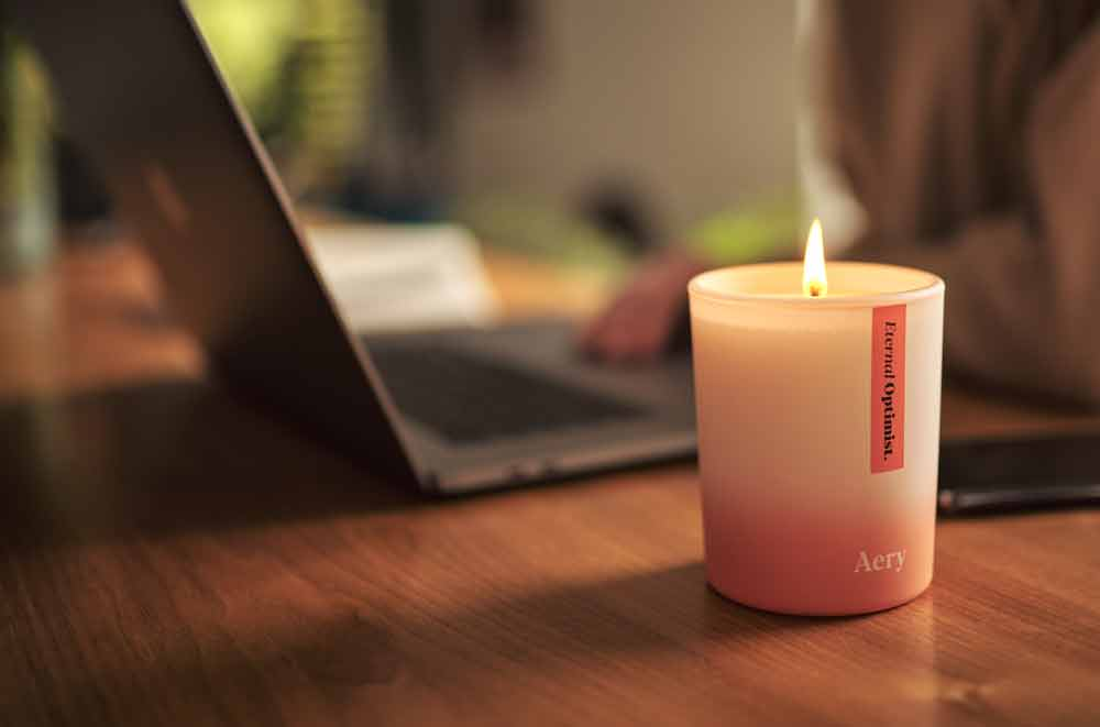 aery living soy wax candle on desk next to laptop while person works