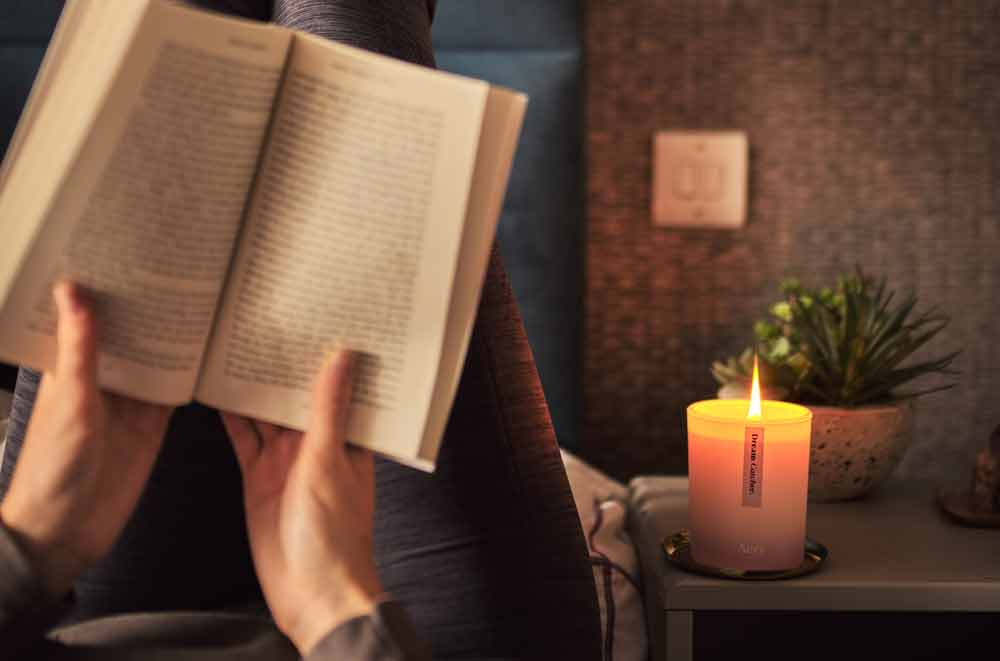 dream catcher lavender scented candle from aery living on a beside table with person laying in bed reading a book