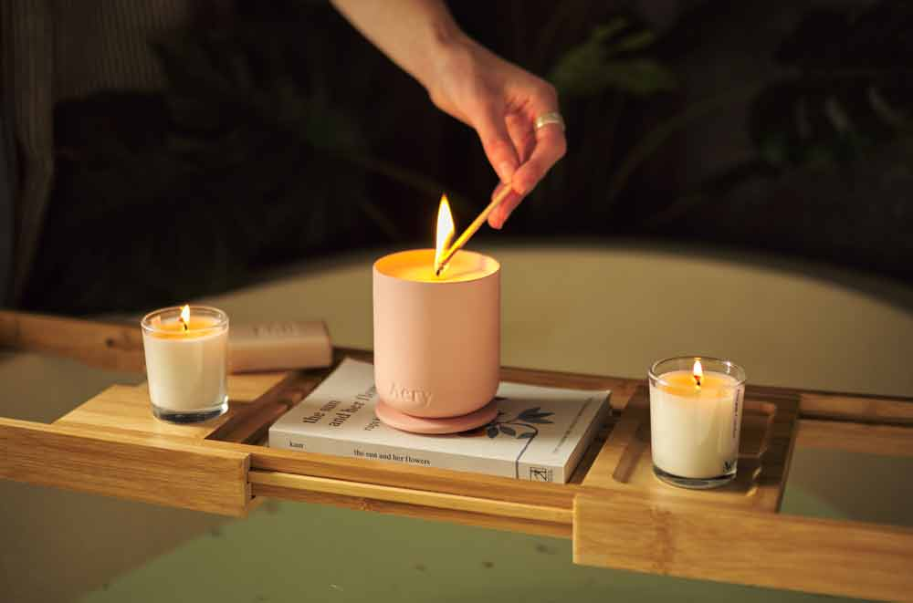 rose scented candle by aery living being lit by a person on top of a bath caddy with books and miniature candles