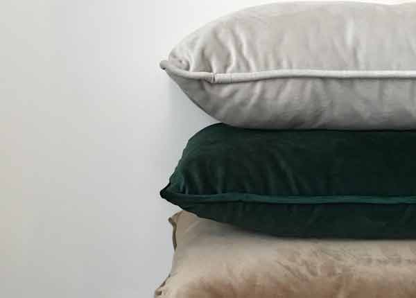 decorative image of three different coloured velvet cushions stacked on one another