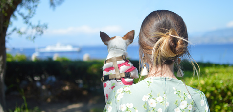 girl holding dog staring at the sea