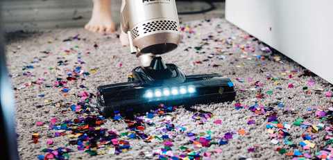 someone using a vacuum to clean confetti off carpet