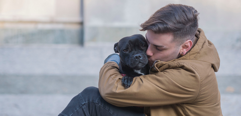 man hugging and kissing black dog