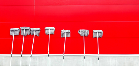 a lot of mops propped up again a bright red wall