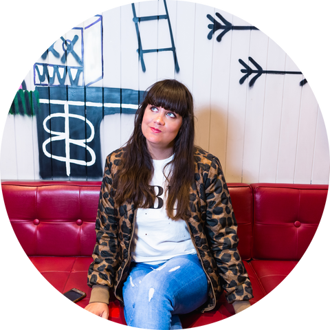 Emma from Cherry Pie Makes sitting on a red sofa with a wall decorated with graffiti behind her