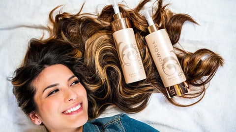 woman with brown hair with shampoo and conditioner bottles