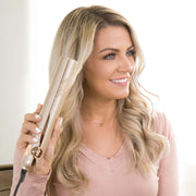 Smiling Millennial female using the TYME Iron Pro to create curls in her blonde, long hair.