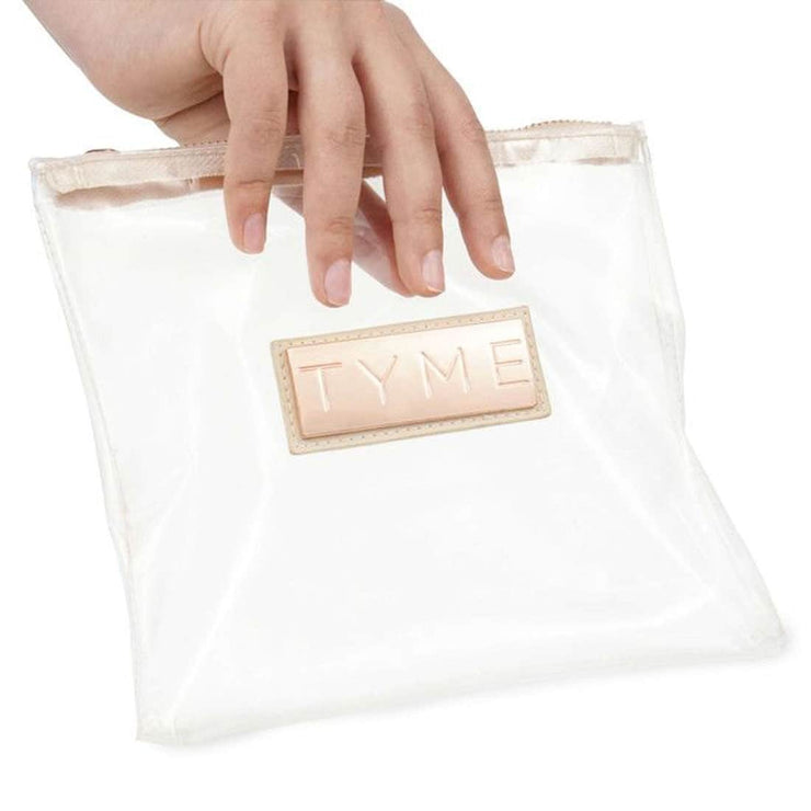 Small zippered clear product travel bag with TYME name on the front on a rose gold emblem.