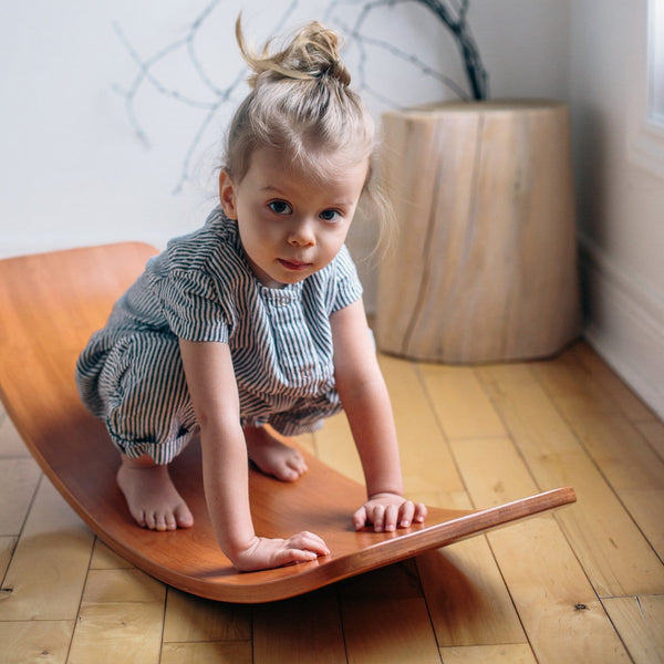 100% Bamboo Kinderboard with no hidden veneer girl sitting and swinging | Eco Toys | Kids Educational - The Vegan Town