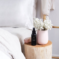 The Goodnight Co Sleep Mist Sweet Dreams 100ml Bottle on natural wood bedside table with flowers and a bed | Online Vegan Store