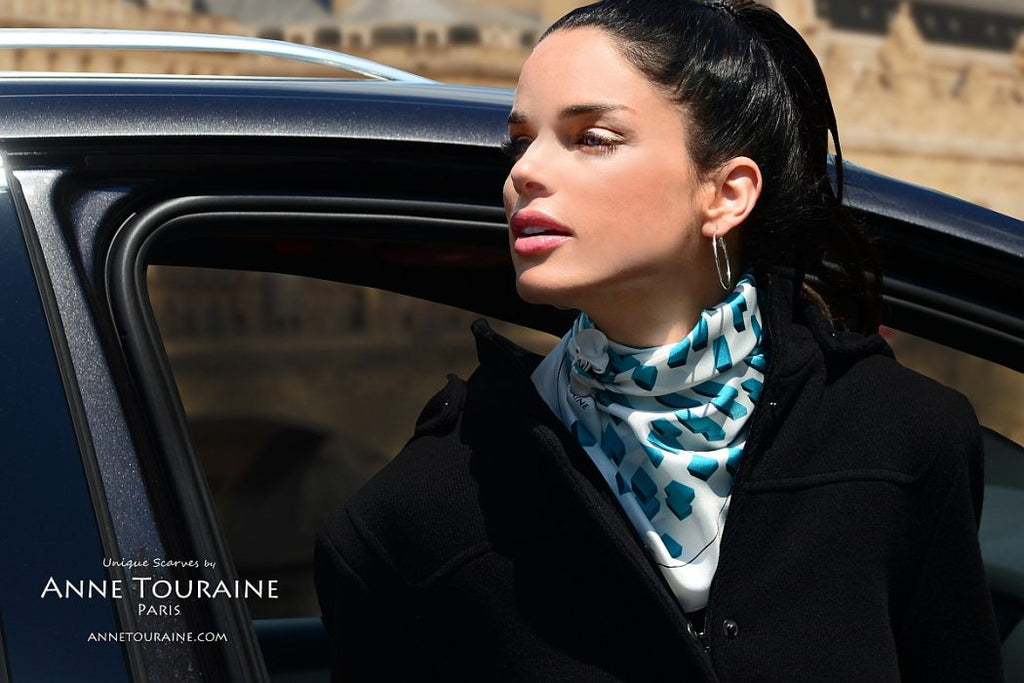 French silk scarves by ANNE TOURAINE Paris™: Teal and white geometric scarf tied as kerchief over a coat and slightly tilted to the side of the neck