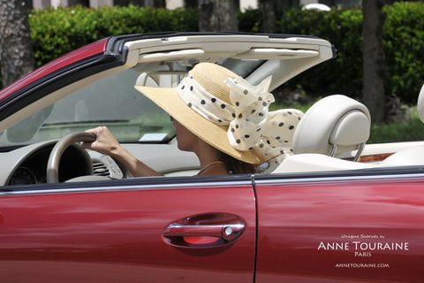 Scarves in the summer: a lightweight polka dot scarf by ANNE TOURAINE Paris™ tied with a bow around a straw hat.
