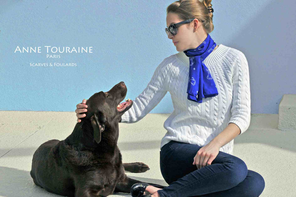Chiffon silk scarves by ANNE TOURAINE Paris™: blue dog pattern scarf wrapped twice around the neck and tied with a tight knot