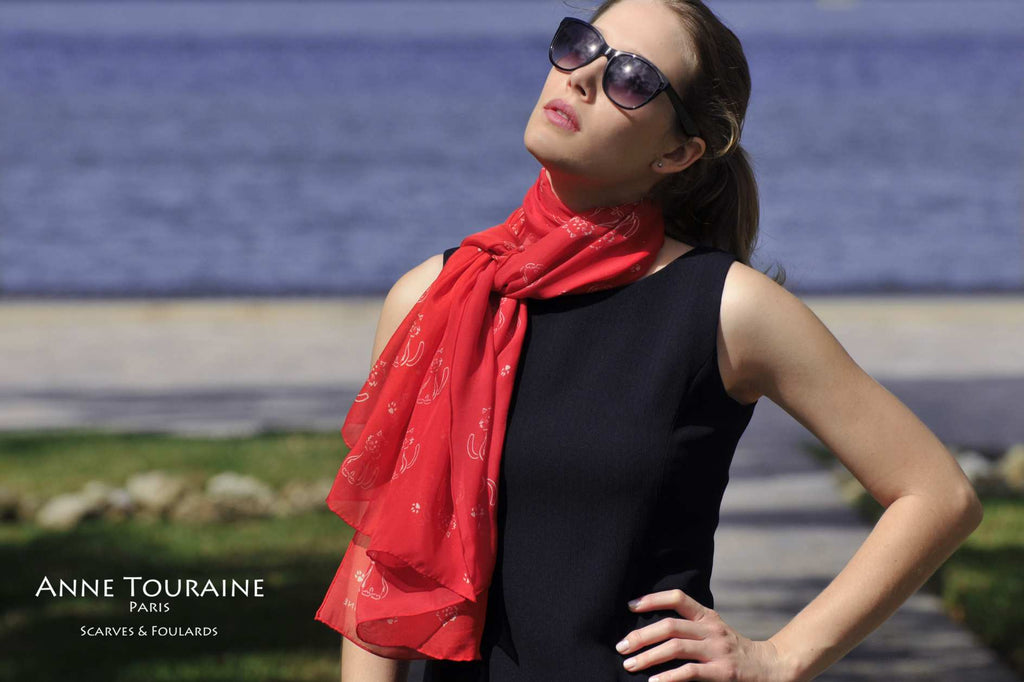 Chiffon silk scarves by ANNE TOURAINE Paris™: red cat pattern scarf wrapped twice around the neck and tied with a loose knot