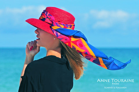 An ANNE TOURAINE Paris™ multicolor silk scarf tied around a red straw hat